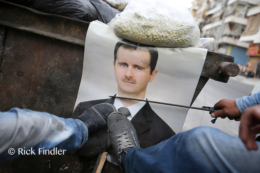 Photographer: Rick Findler..06.10.12 A picture of Syrian President Bashar Assad is kicked and defaced by members of the Free Syrian Army in the city of Aleppo, Syria.