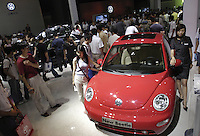 Visitors look at a Volkswagen New Beetle at the Auto China 2004 exhibition in Beijing, China..
