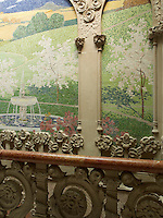 Decorative mosaic panels of lush countryside fill the voids between the carved pillasters on the staircase gallery