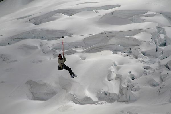 Woman on a zip line in the Alps above Lauterbrunnen, Switzerland.