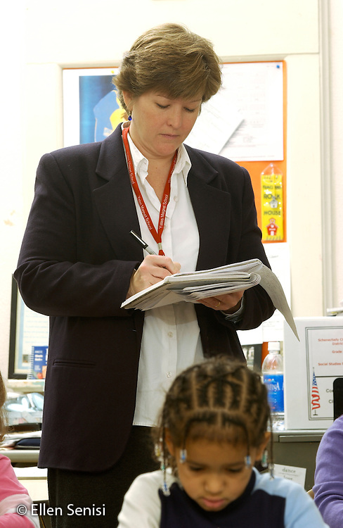 MR / Schenectady, NY.Yates Arts-in-Education Magnet School, Grade 2.Arts-Themed Urban Elementary School.Teacher makes notes on student progress as she walks around the room and checks classwork..MR: Car19.© Ellen B. Senisi