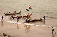 Fisherman land their piogues with the day's catch at Cape Coast Castle, Ghana. Photograph by Peter Randall.