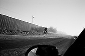 Agua Prieta.Mexico.October 22, 2006..A horse with two riders runs along the US- Mexican border fence at sunrise from the Mexican side. The fence is to deter immigrants from entering the USA illegally at the Douglas port of entry..