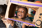 Education Preschool 3-4 year olds boy looking through tv or computer made from cardboard box