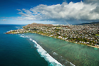 An aerial view of the Kahala district and Diamond Head on O'ahu, with a rainbow in the distance.