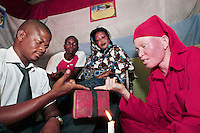 """28 year old Doctor Rama is a mganga, or traditional healer, in a village near Dar Es Salaam. The fact that tens of albinos have been murdered in Northern Tanzania on the orders of witch doctors makes him very sad. """"They targeted them for their body parts which are then used in witchcraft. But those men have nothing to do with my profession,"""" says Rama. """"They want their clients to believe that potions made from albino legs, hair, hands, skin, and blood can make them rich. Of course that is complete nonsense and criminal."""" But Rama admits that for certain magic potions he also needs something with a white color. But the flesh of a coconut or the skin of a white goat will do. Discrimination against albinos is a serious problem throughout sub-Saharan Africa, but recently in Tanzania albinos have been killed and mutilated, victims of a growing criminal trade in albino body parts fuelled by superstition and greed. Limbs, skin, hair, genitals and blood are believed by witch doctors to bring good luck, and are sold to clients for large sums of money, carrying with them the promise of instant wealth."""