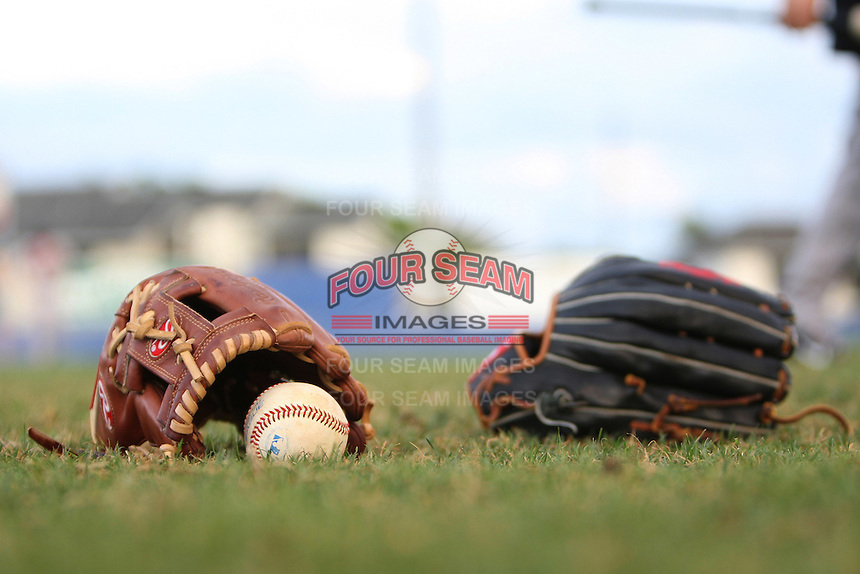 Illinois State Redbirds gloves and baseball laying on the field before a game against the Western Michigan Broncos at Chain of Lakes Stadium on March 10, 2012 in Winter Haven, Florida.  Illinois State defeated Western Michigan 10-9.  (Mike Janes/Four Seam Images)