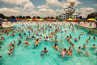 Swimmers cool off in the 20-acre Boomerang Bay water park at Carowinds theme Park near Charlotte, NC. Seen here is Bondi Beach, a 600,000-gallon, 34,000 square-foot wave pool that provides a fresh-water surf-like experience. The water attractions are part of Carowinds, a 112-acre theme park (amusement park) located on the state lines between North Carolina and South Carolina. The theme park is a popular summer Carolina attraction, one of three major theme parks in the Carolinas.