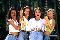 Great friends having fun on swing with women in their 20s and many different ethnic types smiling Black Hispanic