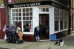 Mobility vehicle disabled older elderly man Margate Kent outside Charity shop for Pilgrims Hospices. 2014 2010s UK England