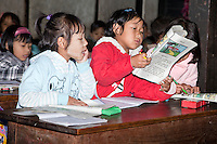 Myanmar, Burma, Kalaw.  Elementary School Classroom and Burmese Children.  Girls Reading.