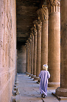 Man dressed in traditional clothing walking in between columns at the Temple of Edfu, Edfu, Egypt.