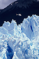 AJ2045, glaciers, Patagonia, Argentina, Andes, A helicopter looks tiny flying over the massive Moreno Glacier which rises 60 meters above lake level in Parque Nacional de los Glaciares (National Park) in Patagonia.