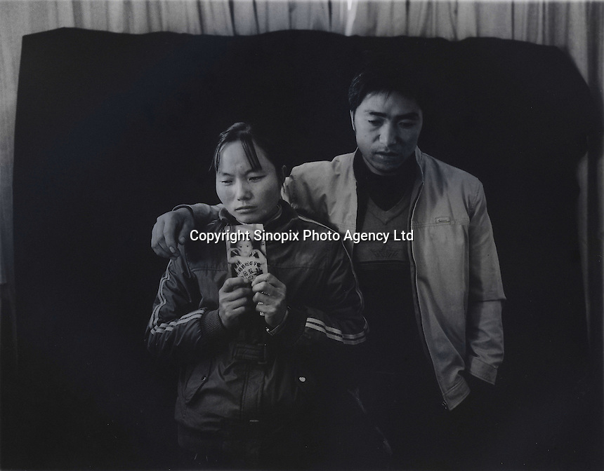 """Mr and Mrs Ma holds a picture of her son Ma Purei, 3 and half years old,  who was stolen  March 22nd  2004.  The message reads, """"Papa and Mama are hoping that you will come home soon.""""  Mrs Ha and Mrs Ma is one of thousands of migrant mothers whose children have been stolen and sold to rich families desperate for a boy. Families are limited to a single child under the China's ruthless One Child Policy...PHOTO BY SINOPIX"""