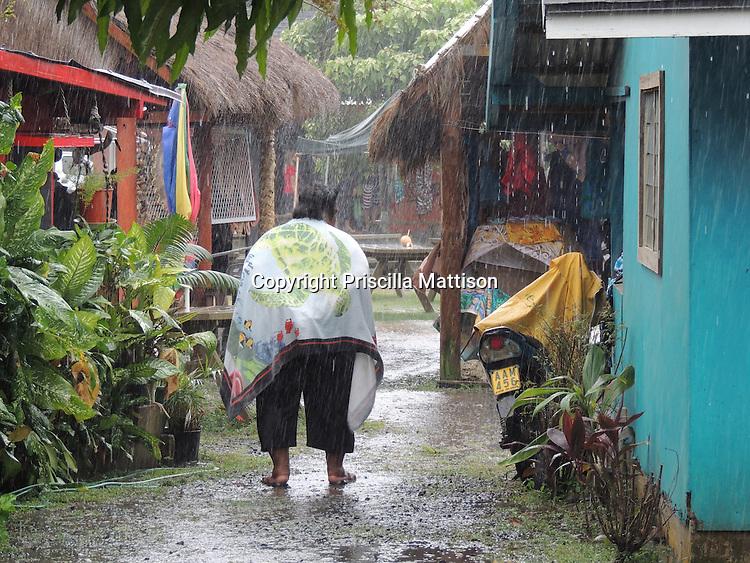 Rarotonga, Cook Islands - September 22, 2012:  A woman makes her way through the Punanga Nui Market during a downpour.