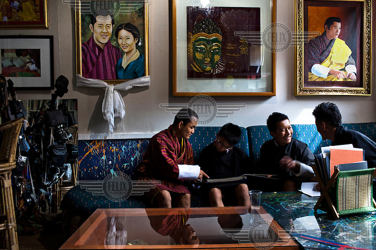 A man gives informal art classes to young children at Vast Art Gallery in downtown Thimpu.  A portrait of the king hangs on the wall above them.