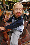 Boy on a saddle eating ice cream
