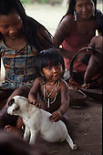 Pikany Village, Brazil. Kayapo mother and girl painted with black and red body paint design; pet dog; Xingu reserve.