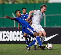 Matthew Dunn (5) of the United States is tackled by Adrian Diz (4) of Cuba during the first day of the group stage at the CONCACAF Men's Under 17 Championship at Catherine Hall Stadium in Montego Bay, Jamaica. The United States defeated Cuba, 3-1.