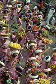 Rio de Janeiro, Brazil. Carnival samba school; sambistas carrying baskets of fruit, wearing pink.