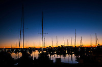 The sun has set at the marina leaving Venus to provide a single bright dot in the sky over the naked sailboat masts.