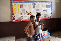 Two kids in a Pioneers of the Revolution center watch a tablet computer in downtown Havana