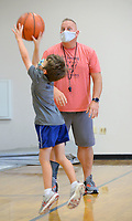 T.J. Barnes, athletics director at St. Joseph Catholic School, encourages campers Tuesday, Aug. 3, 2021, as they run through a layup drill during basketball skills camp at the school in Fayetteville. The camp is hosting about 100 students from kindergarten to eighth grade for a week of basketball fundamentals. Visit nwaonline.com/210803Daily/ for today's photo gallery.<br /> (NWA Democrat-Gazette/Andy Shupe)