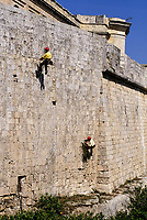 Mdina, Malta.  Firemen Rappel down the City Walls of Mdina to Remove Weeds and Bushes.  If left to grow, these weeds would cause the wall's stones to crack and crumble, undermining the integrity of the wall.