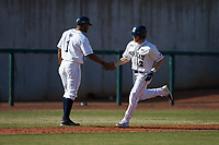 Conlin Hughes (2) of the Penn State Nittany Lions slaps hands with assistant coach Andre Butler (1) while rounding third base against the Xavier Musketeers at Coleman Field at the USA Baseball National Training Center on February 25, 2017 in Cary, North Carolina. The Musketeers defeated the Nittany Lions 10-4 in game one of a double header. (Brian Westerholt/Four Seam Images)