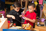 Education preschool 4-5 year olds pretend play two boys playing together at toy stove transferring play food