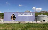 Nederland  Zaanstad Assendelft Nauerna - 2019.  De Nauernasche Polder, tussen de woonbebouwing Nauerna en het Noordzeekanaal, is sinds begin jaren tachtig in gebruik als vuilstort van de firma Afvalzorg. Wegens problemen met afvalverwerkingsbedrijf AEB uit Amsterdam, wordt hier de komende tijd ook afval uit Amsterdam gestort. Waterzuivering. De waterzuiveringsinstallatie vormt functioneel een belangrijk onderdeel in de waterhuishouding van het totale gebied binnen de Nauernasche Polder met het kunstmatige industrielandschap van stortlocatie Nauerna. De nieuwe hal is vormgegeven als een box, waarbij HWA's, noodoverstorten en roosters uit het zicht, aan de achterzijde van het gebouw zijn geplaatst. Het gebouw is een ontwerp van Arc2.  Foto Berlinda van Dam / Hollandse Hoogte