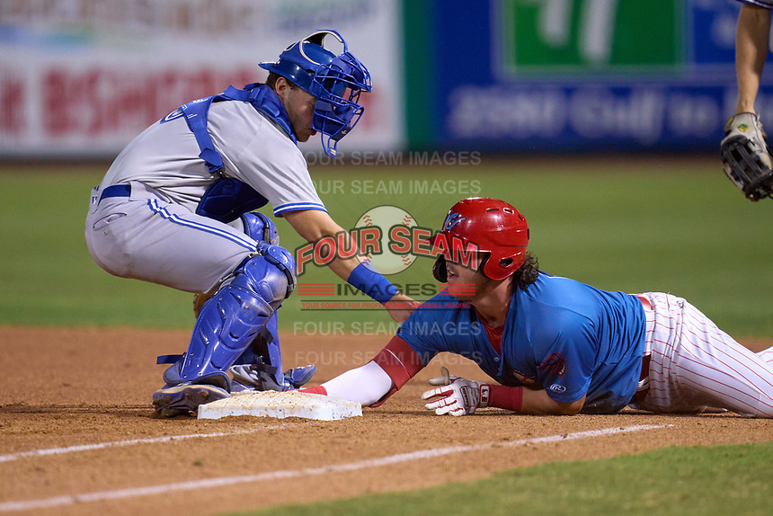Clearwater Threshers Rixon Wingrove (52) dives back into first base as catcher Zach Britton (6) attempts to apply a tag during a game against the Dunedin Blue Jays on May 18, 2021 at BayCare Ballpark in Clearwater, Florida.  (Mike Janes/Four Seam Images)