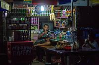 Bali, Indonesia.  Shopkeeper Having Early-morning Bread and Coffee, Jimbaran Market.