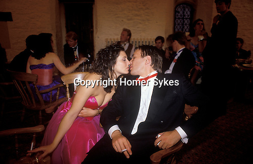 Cirencester, Gloucestershire. 1997  <br />  With the obligatory ciggie in hand, a young couple demonstrate their fondness for each other at the Cirencester Royal Agricultural College end of year ball.
