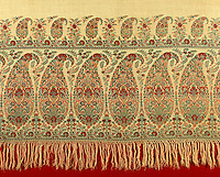 In the dining room of a house in the country the detail of a tasselled and embroidered tablecloth in a paisley design