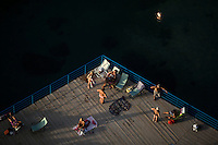 Locals enjoy the sunlight on a deck overlooking the Gulf of Naples on Thursday, Sept. 17, 2015, in Sorrento, Italy. (Photo by James Brosher)
