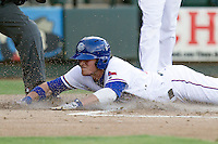 Round Rock Express outfielder Jim Adduci (24) slides into home plate against the Oklahoma City RedHawks during the Pacific Coast League baseball game on August 25, 2013 at the Dell Diamond in Round Rock, Texas. Round Rock defeated Oklahoma City 9-2. (Andrew Woolley/Four Seam Images)