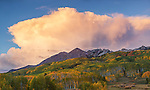 Gunnison National Forest, CO: Storm cloud in evening light over the Ruby Range with early fall colors on aspen hillsides