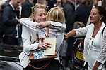 """© Joel Goodman - 07973 332324 . 28/08/2015 . Salford , UK . Mourners hug outside the church after the service . The funeral of Paul Massey at St Paul's CE Church in Salford . Massey , known as Salford's """" Mr Big """" , was shot dead at his home in Salford last month . Photo credit : Joel Goodman"""