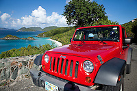 Trunk Bay overlook and tourist with NY baseball cap in a red jeep.<br /> St. John<br /> Virgin Islands National Park