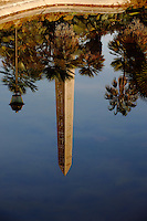 Rome, villa Torlonia: The reflected image of an obelisk, of a street lamp and of the surrounding trees on the perfectly flat water surface of a basin in villa Torlonia.