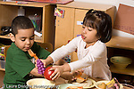 Education preschool 4 year olds pretend play boy and girl in kitchen area playing with colorful plastic vegetables and food talking and interacting horizontal
