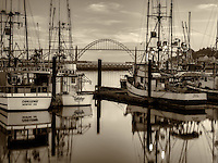 Yaquina Bridge at Newport Harbor with fishing boats and sunset clouds. Newport, Oregon