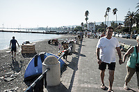 A tourist couple walking on the corniche past the refugees on a gravel beach.  Kos, Greece. Sept. 5, 2015