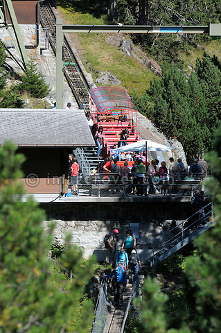 Switzerland, Western Europe, Grimsel region, nr. Guttannen, Gelmerbahn funicular. Boarding at the lower terminus. Note: No releases available. --- Info: The Gelmer cable car funicular railway with a maximum incline of 106 percent is Europe's steepest cable car. The Gelmer Railway was built in the 1920s to help with the construction of the Lake Gelmer water reservoir dam. Originally used for freight the cable car was converted to a passenger railway in 2001. The 12 minutes and one kilometer long ride in the open carriages overcomes a 450 meters height difference and takes one up to Lake Gelmer at an altitude of 1860 meters above sea level. The region where the reservoir is located is the starting point for hikes and mountain tours.