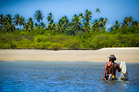 Fisherman wading with his net in the turquoise Atlantic Ocean, in front of Porto de Galinhas sand beach and palm trees, in Ipojuca Pernambuco, Brazil