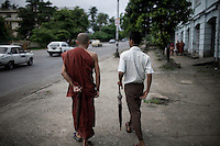 A monk walks and talks with a friend in Rangoon. It has become increasingly difficult, following the anti-government protests of 2007, which became known as the Saffron Revolution, for monks to meet with people in large numbers.