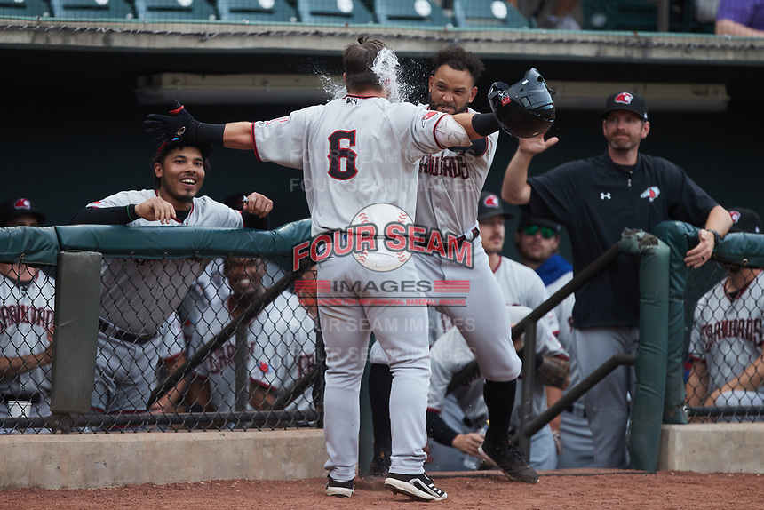 Trey Hair (6) of the Hickory Crawdads has water thrown in his face as he returns to the dugout after hitting a home run against the Winston-Salem Dash at Truist Stadium on July 7, 2021 in Winston-Salem, North Carolina. (Brian Westerholt/Four Seam Images)