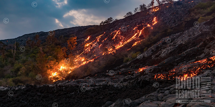 At dusk, lava rivers flow down Pulama Pali (part of Holei Pali), Hawai'i Volcanoes National Park, Puna district, Hawai'i Island, December 2017.