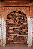 A decorative Indian arched door in a ruined palace, bricked up with stones, Rajasthan, India.